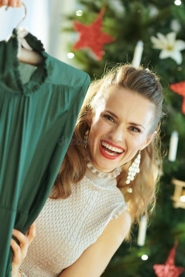显示欢乐绿色圣诞节礼服的愉快的时髦主妇 图库摄影