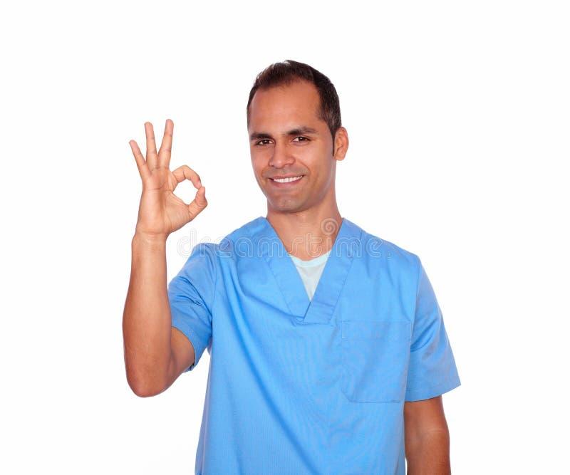 显示正号用手的迷人的护士 免版税库存照片