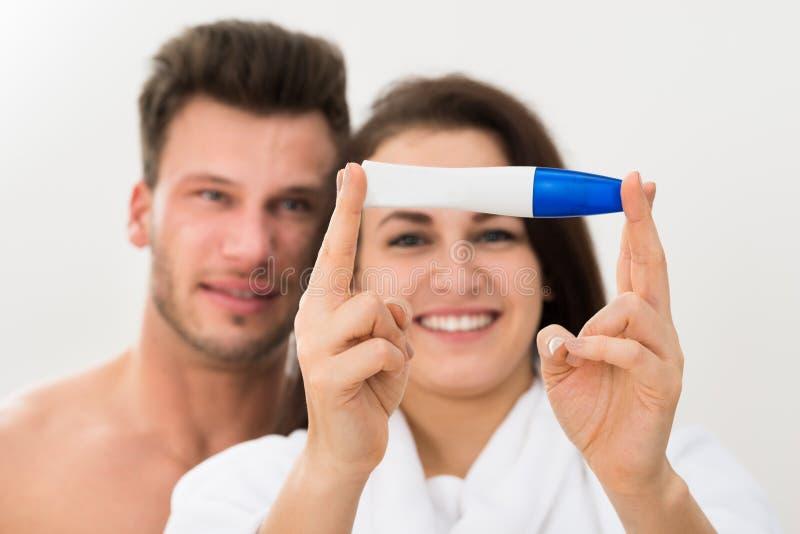 显示正面妊娠试验的夫妇 库存图片