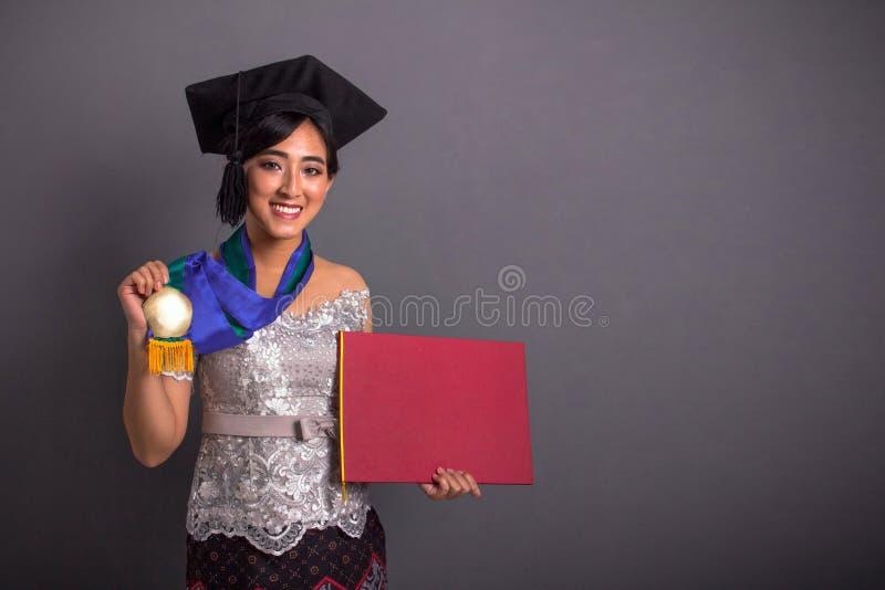 显示毕业的她的奖牌和证明美女 库存图片