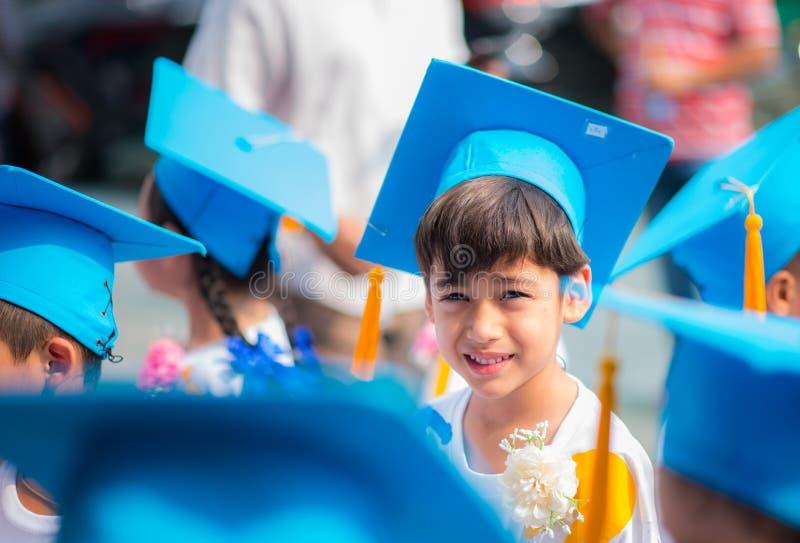 显示毕业的hhat制服的小男孩在幼儿园学校 免版税图库摄影
