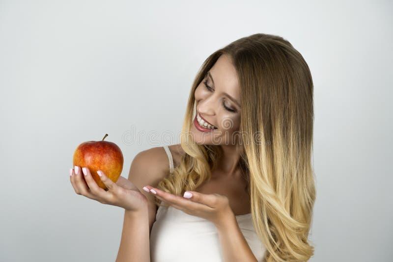 显示水多的红色苹果的微笑的白肤金发的可爱的妇女拿着果子在一手被隔绝的白色背景 免版税图库摄影