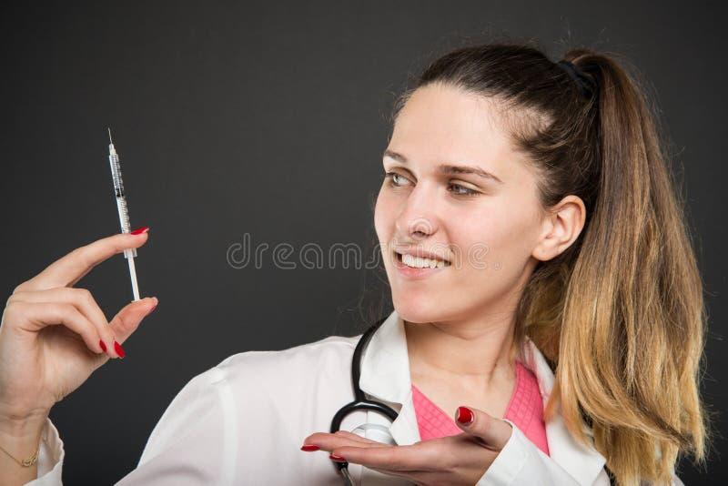 显示注射器的女性医生侧视图 免版税库存图片
