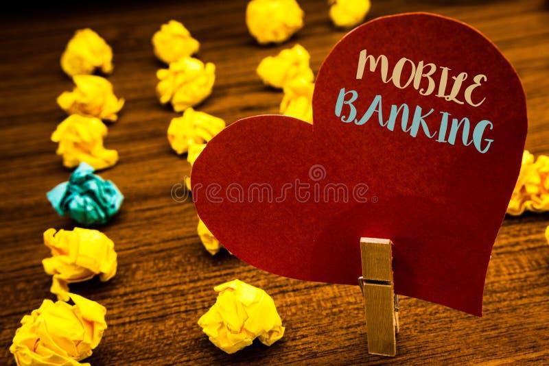 显示流动银行业务的文本标志 概念性照片网上现款支付和交易真正银行发短信给红色心脏木夹子de 库存照片