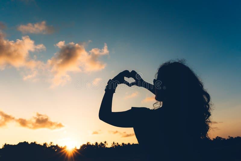 显示爱,做心形的姿态用手和享受日落的妇女剪影在异乎寻常的手段 免版税库存图片