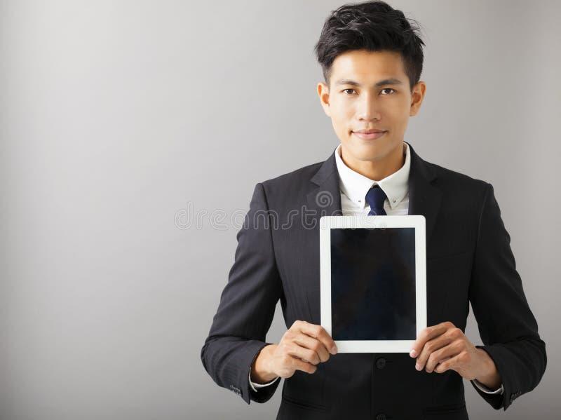 显示片剂个人计算机的微笑的商人 免版税图库摄影