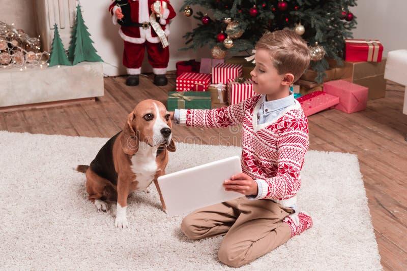 显示片剂的男孩对在圣诞节的狗 免版税图库摄影