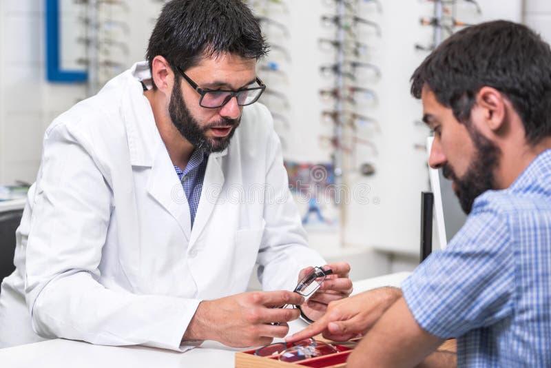 显示用不同的玻璃的眼科医生一个盘子对顾客 库存图片