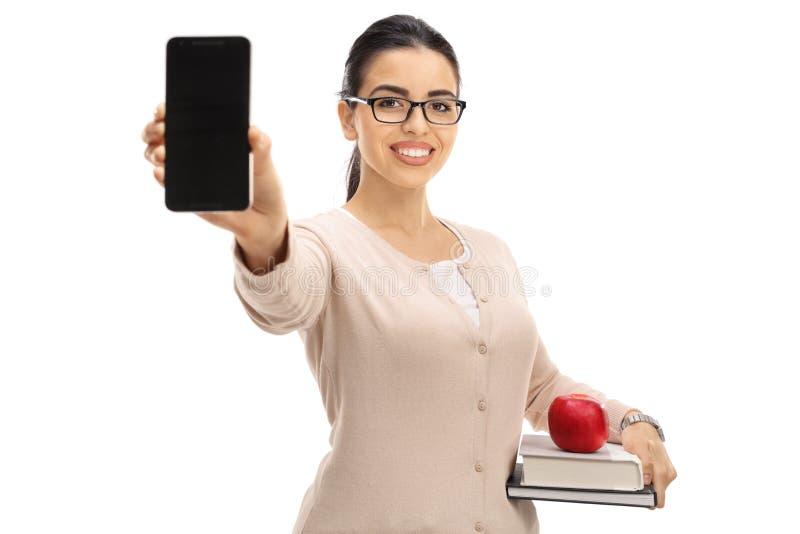 显示电话和微笑的女老师 免版税库存照片