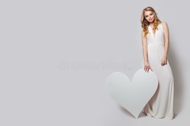 显示白色心脏背景的美女 在完善的白色礼服的好的模型 库存照片
