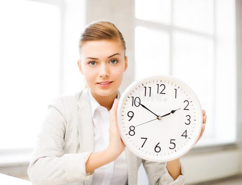 显示白色时钟的可爱的女实业家 库存图片