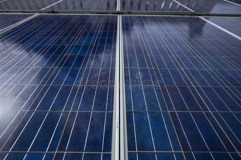 显示的蓝色太阳能电池盘区它的表面网格线和纹理 盘区反对在中午时间的太阳光有阴影关于 库存图片