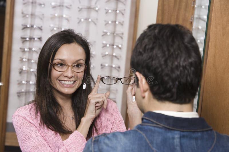 显示眼睛玻璃的妇女对人 免版税图库摄影