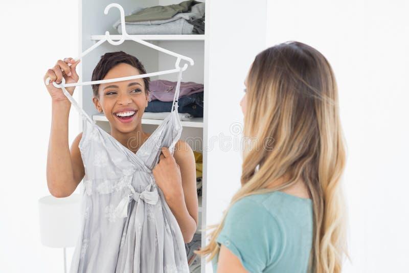 显示礼服的快乐的妇女对她的朋友 免版税库存照片