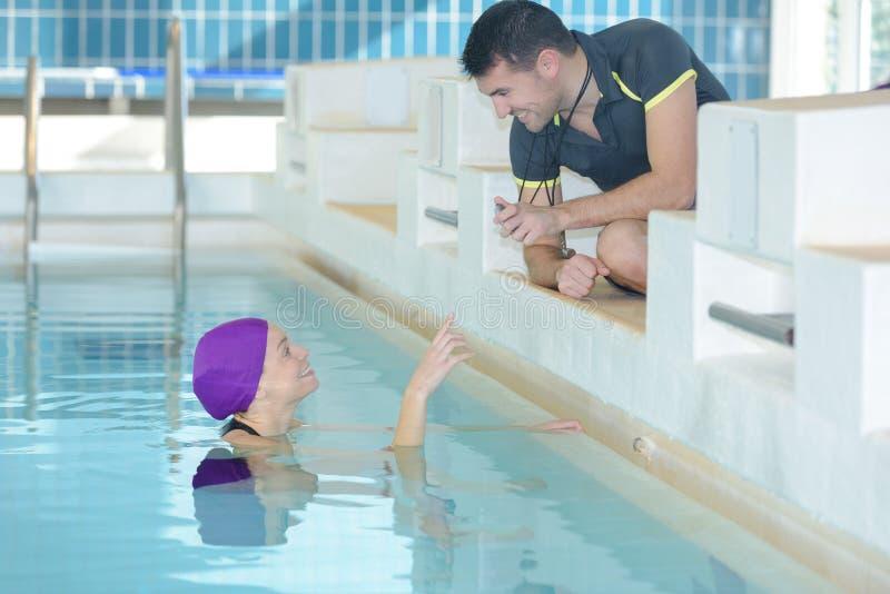 显示秒表的微笑的教练员在游泳者有空的中心 免版税库存照片