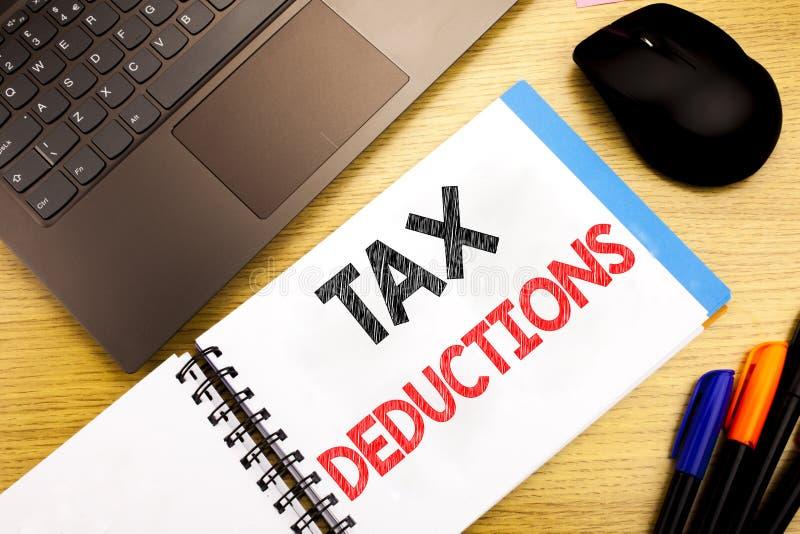 显示税收减免的手写的文本说明 企业在笔记写的财务接踵而来的税钱扣除的概念文字 免版税库存照片