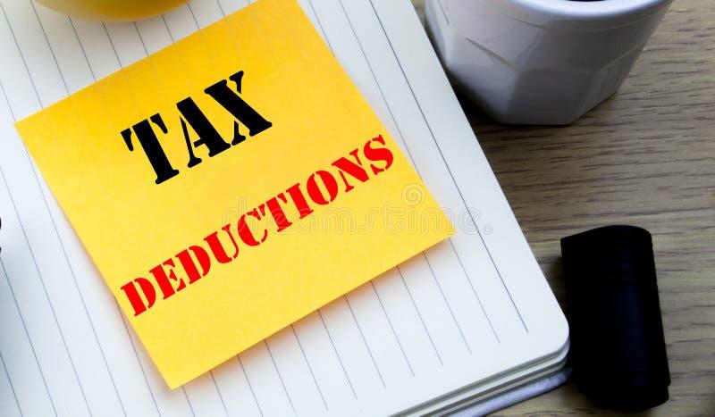 显示税收减免的文字文本 财务接踵而来的税钱扣除书面稠粘的笔记空的纸的, Wo企业概念 库存照片