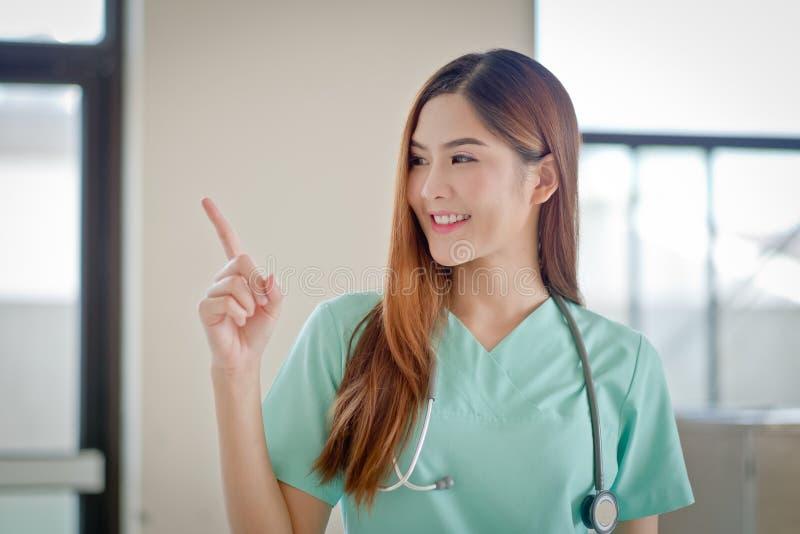 显示空白的区域f的愉快的微笑的年轻美丽的女性医生 免版税图库摄影