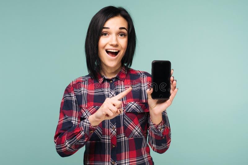 显示空白的智能手机屏幕和指向对此的格子衬衫的惊奇的愉快的深色的妇女,当看照相机时 库存照片