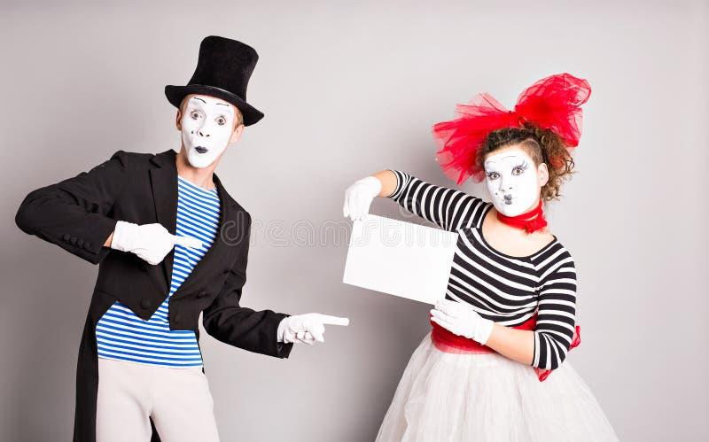 显示空白的牌,与文本或口号的copyspace区域的愉快的微笑的年轻演员画象,反对灰色 免版税库存图片