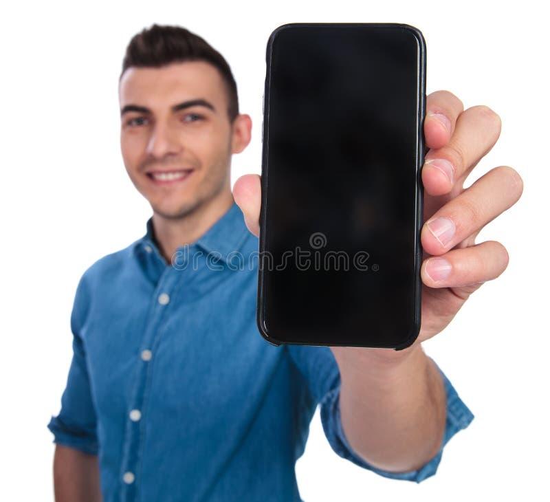显示空白的电话屏幕的微笑的偶然人画象  库存照片