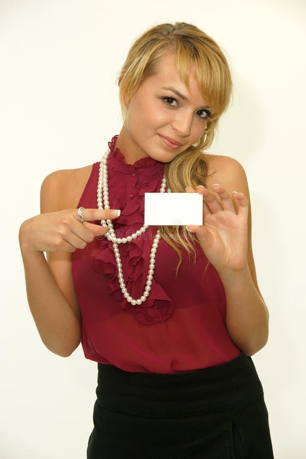 显示空白的白色卡片的年轻白肤金发的妇女 库存图片