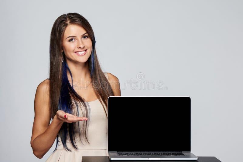 显示空白的黑便携式计算机屏幕的妇女 免版税库存照片