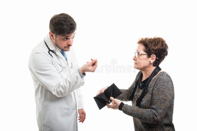 显示空的钱包的女性资深患者对男性医生 免版税库存图片