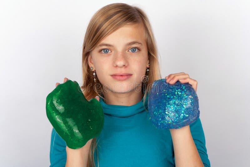 显示绿色和蓝色软泥的少女 免版税库存照片
