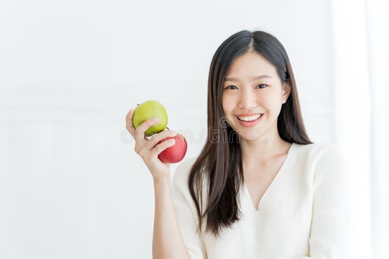 显示绿色苹果和红色苹果,户内画象的年轻亚裔妇女 库存照片