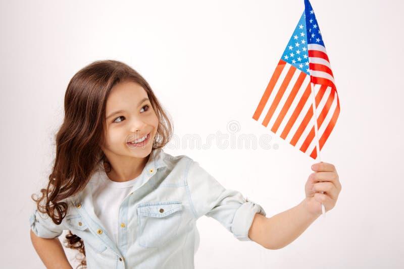 显示美国国旗的高兴小女孩在演播室 库存照片