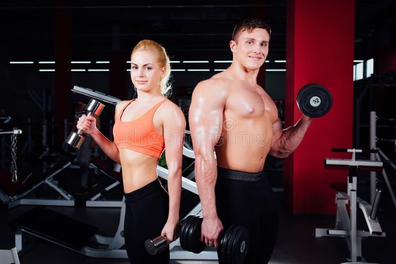 显示肌肉和摆在与哑铃的美好的年轻运动的夫妇在健身房在photoshooting期间 免版税库存照片