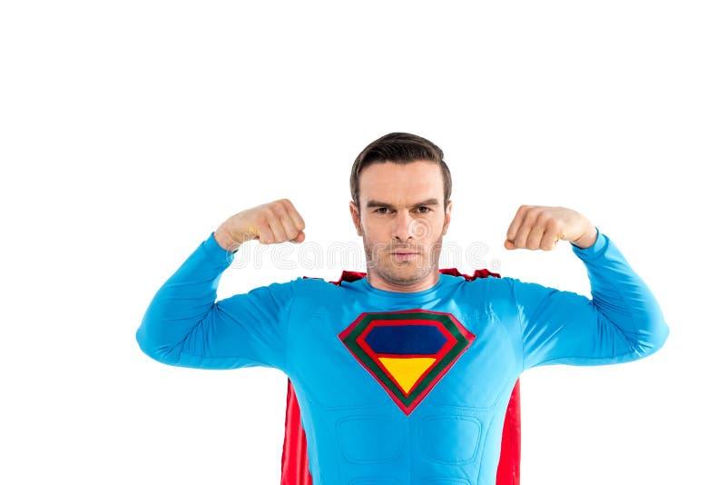 显示肌肉和看照相机的英俊的超级英雄 库存照片