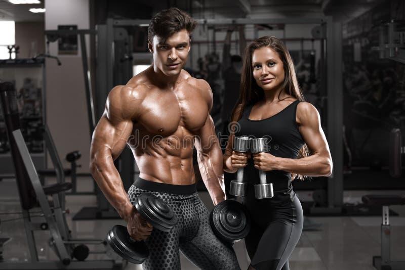 显示肌肉和锻炼的运动的性感的夫妇在健身房 肌肉人和wowan 免版税库存图片