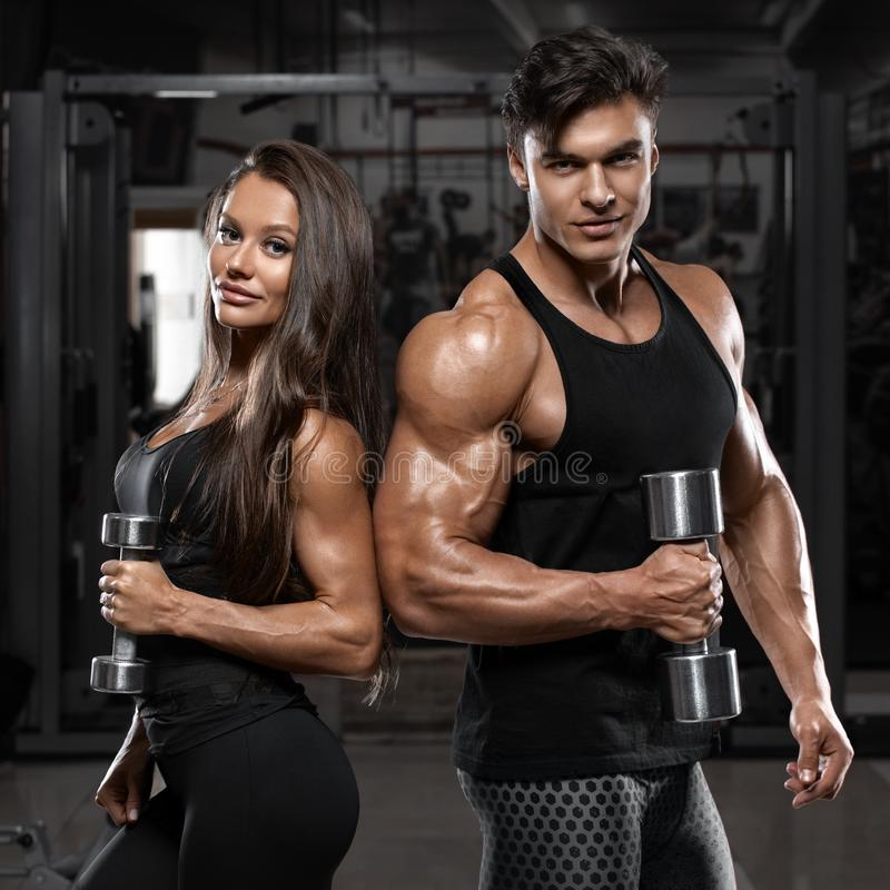 显示肌肉和锻炼的运动的性感的夫妇在健身房 肌肉人和wowan 库存照片