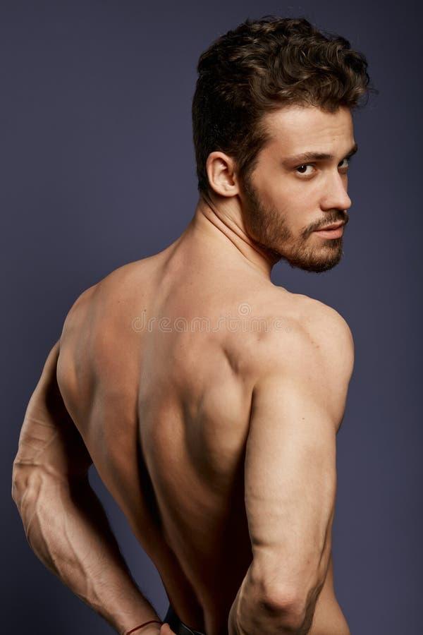 显示背部肌肉,三头肌,latissimus的坚强的帅哥 库存图片