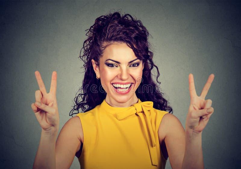 显示胜利或和平标志的黄色礼服的微笑的妇女 免版税库存图片