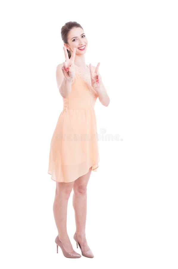显示胜利标志的夏天礼服的美丽的夫人 免版税库存照片