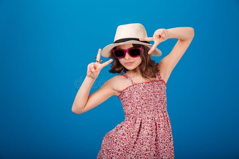 显示胜利标志的帽子的逗人喜爱的嬉戏的小女孩 库存照片