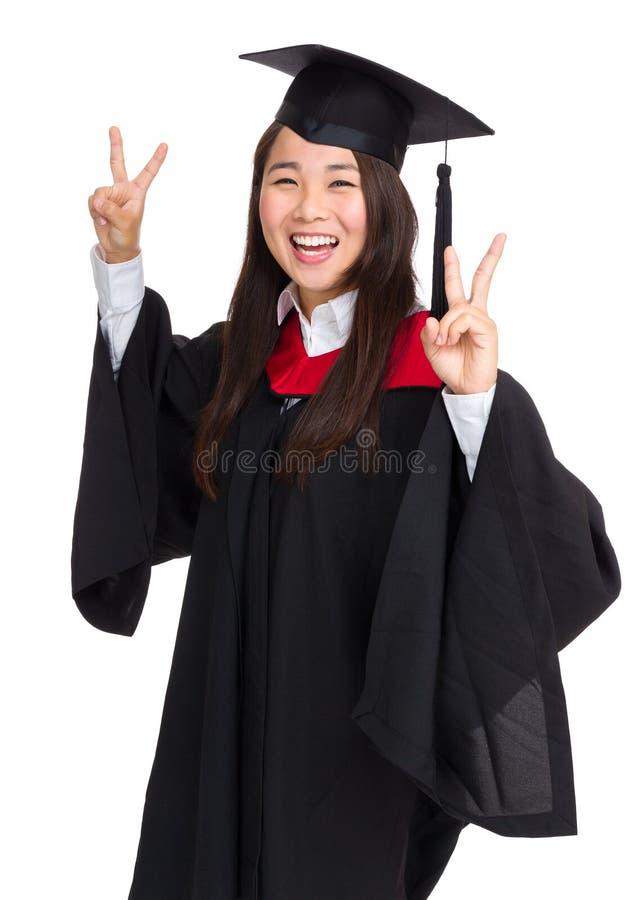 显示胜利标志的毕业生女学生 库存图片