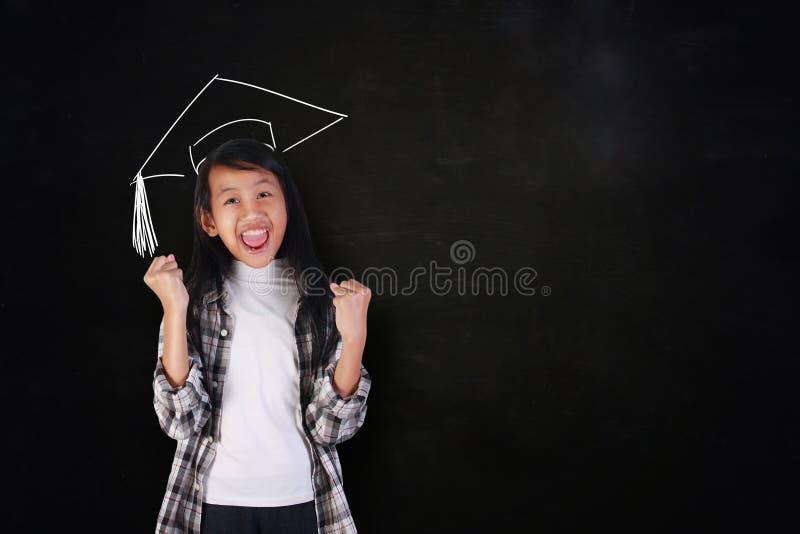 显示胜利的愉快的研究生女孩 免版税库存图片