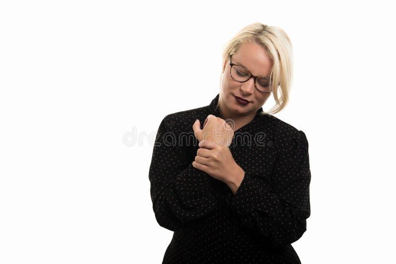 显示腕子痛苦的白肤金发的女老师佩带的玻璃打手势 库存图片
