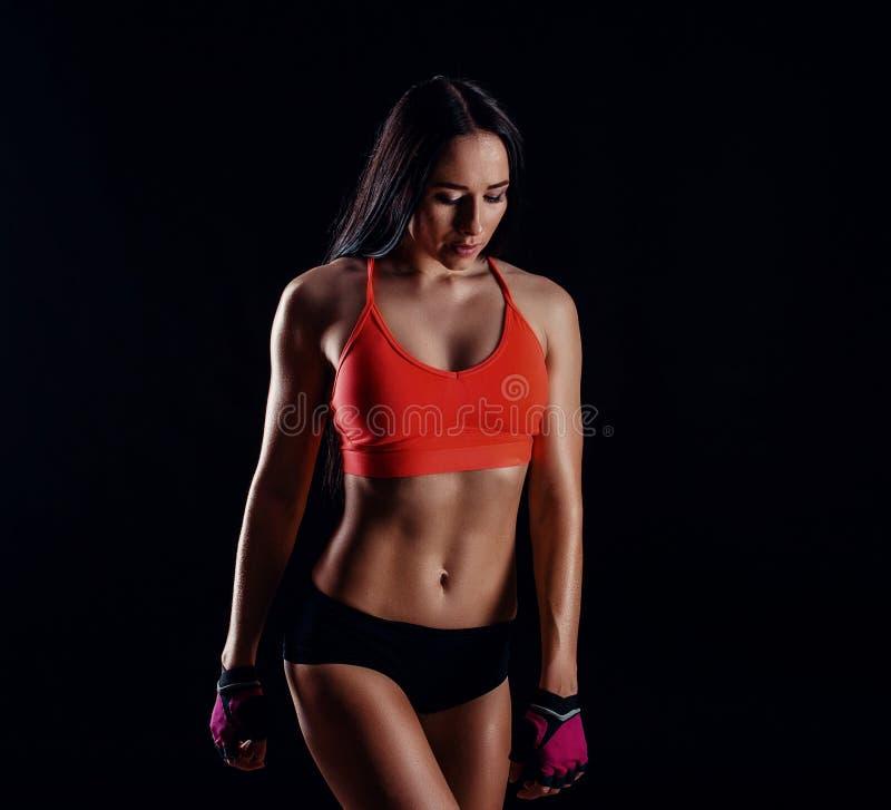 显示腹肌的好性感的健身妇女被隔绝在黑背景 训练的女性身体 库存照片