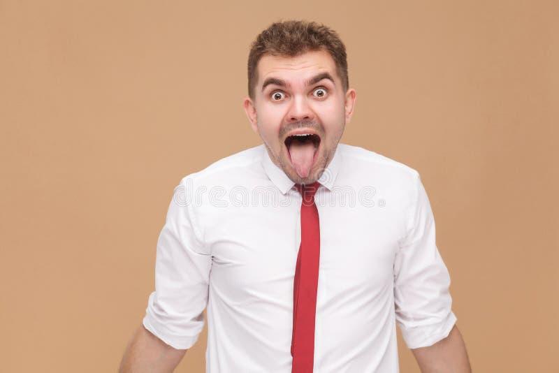 显示舌头的疯狂的商人特写镜头画象  免版税库存图片