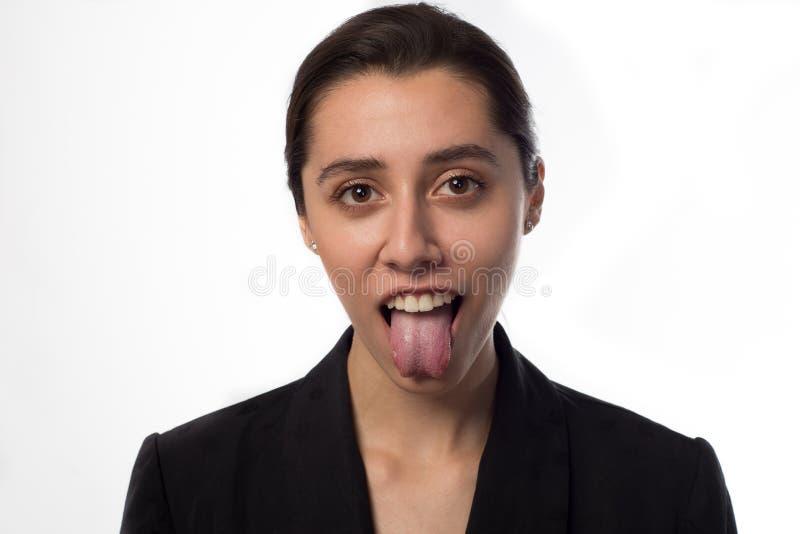 显示舌头的凉快的女商人 免版税库存图片