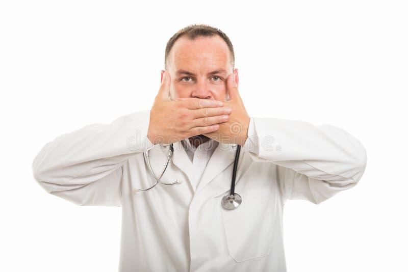 显示覆盖物嘴姿态的男性医生画象 免版税库存照片