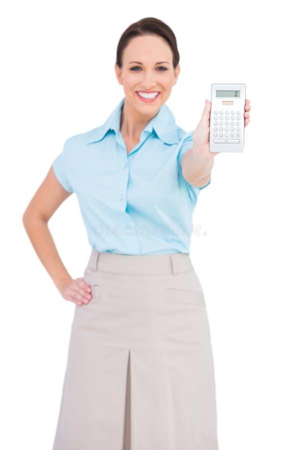显示计算器的微笑的优等的女实业家 图库摄影
