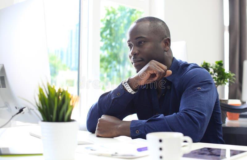 显示计算机的一位愉快的非裔美国人的企业家的画象在办公室 库存照片