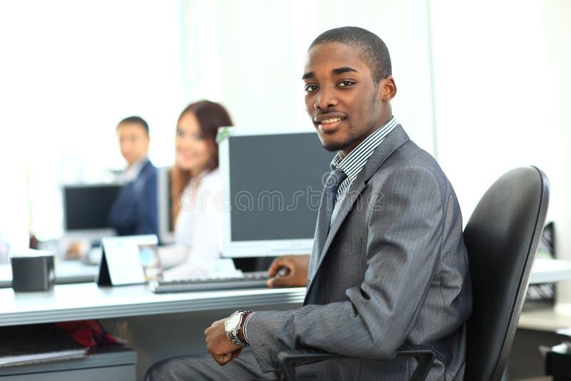 显示计算机膝上型计算机的非裔美国人的企业家在办公室 库存照片