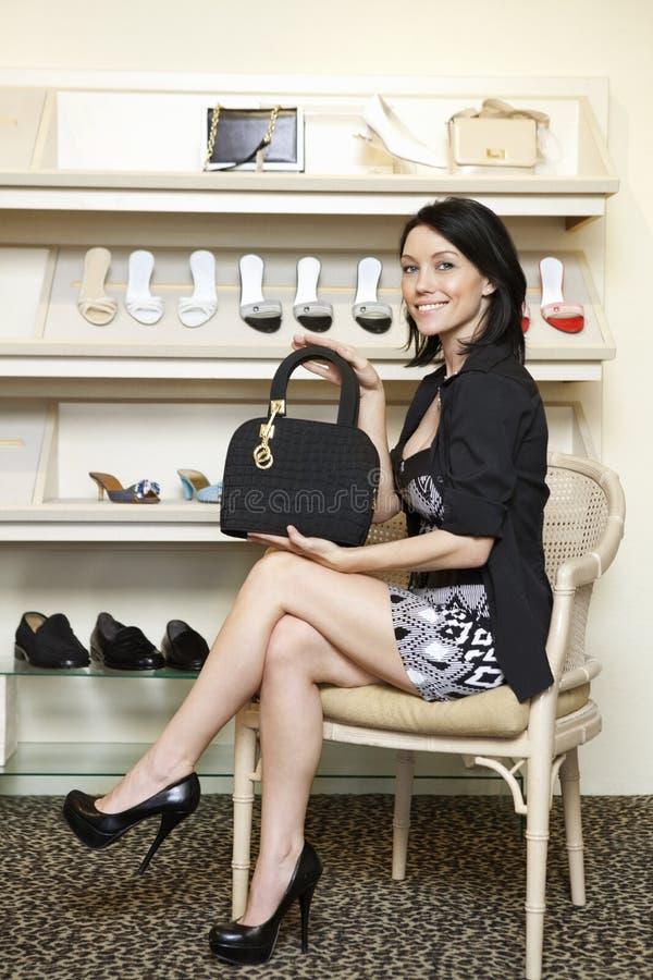 显示设计师提包的一名中间妇女的画象在鞋类商店 免版税库存图片